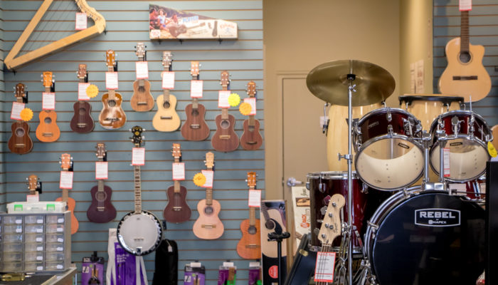 Ukuleles and drum sets in display.
