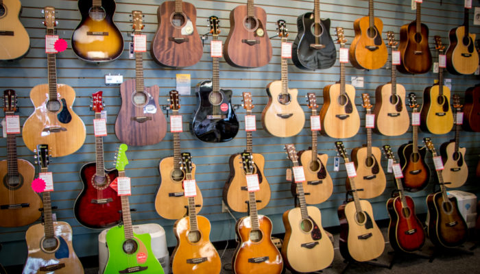 A large selection of acoustic guitars of different colors on display.