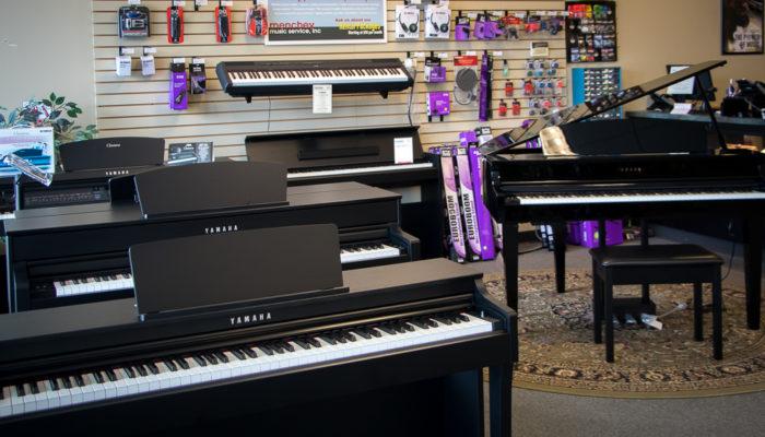 Yamaha Clavinova digital pianos with keyboard accessories behind them.