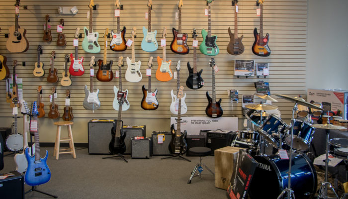 Electric guitars displayed on a wall with amplifiers beneath them.