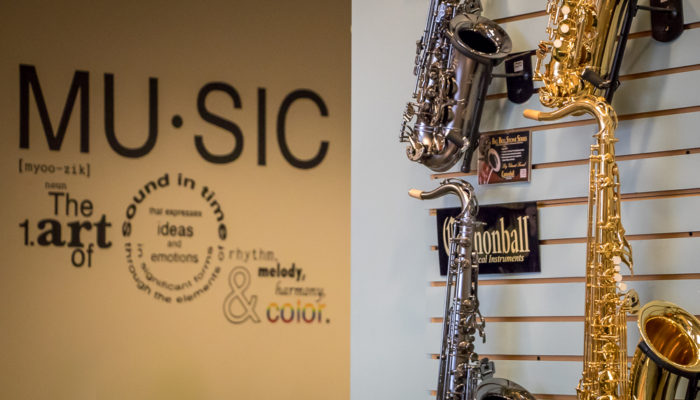 Four saxophones with a music quote on the wall behind them.