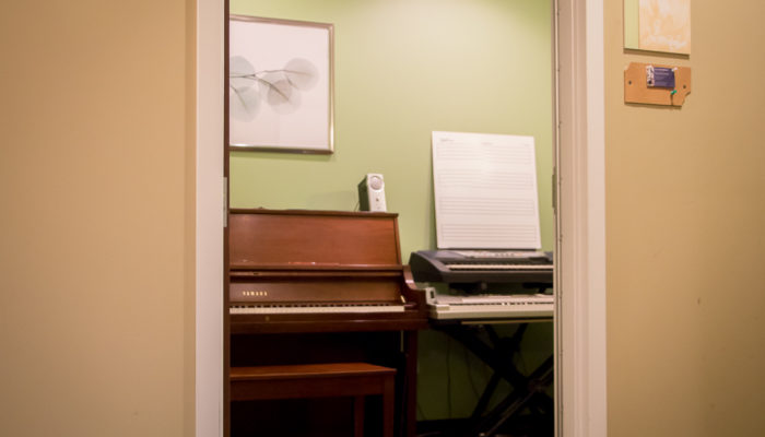 Lesson studio with a piano and two keyboards.