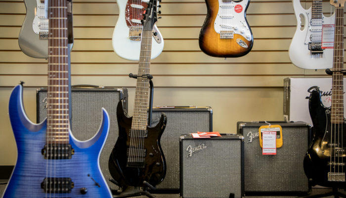 Electric guitars hung on wall with amplifiers beneath them.
