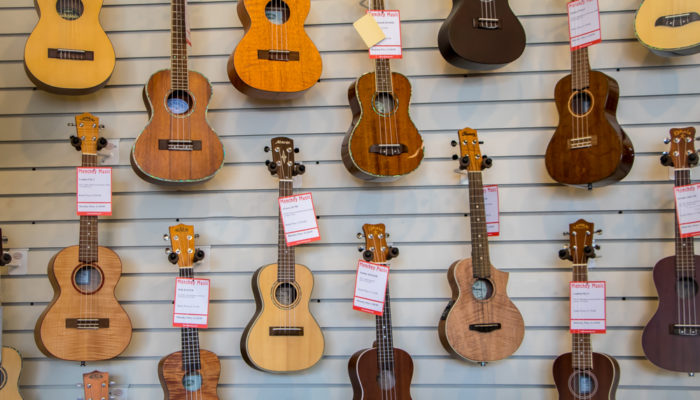 Wall display of ukuleles with varied wood finishes.