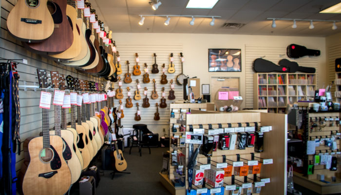 Acoustic and electric guitars by Yamaha, Ibanez and Fender hanging on wall.