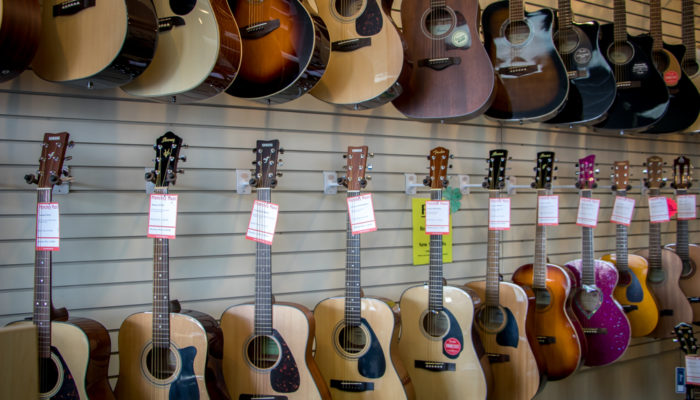 Wall display of Fender, Ibanez and Yamaha acoustic guitars.