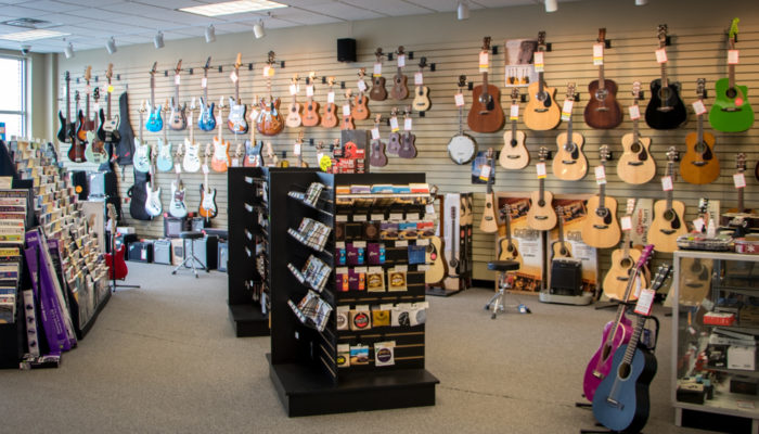 Acoustic guitars and guitar accessories such as strings on dispay.