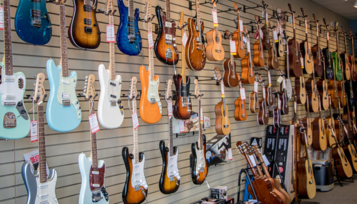Electric guitars in many colors on wall display.