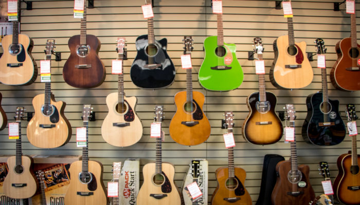 Acoustic guitars in different colors displayed on wall.
