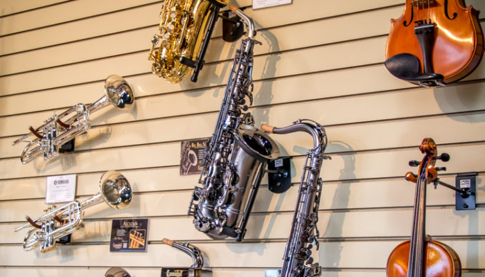 Intermediate and professional band and orchestra instruments hung on a wall display.