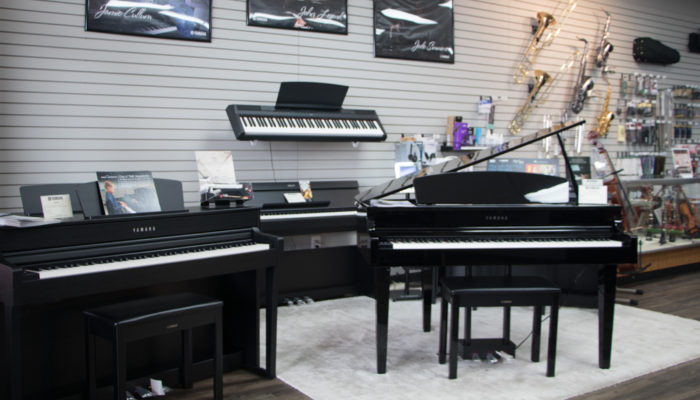 Display of Yamaha Clavinova digital pianos and keyboard.