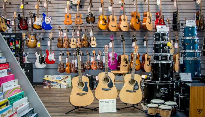 Large selection guitars displayed on floor stand and wall.