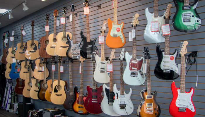 Electric and acoustic guitars on wall display.