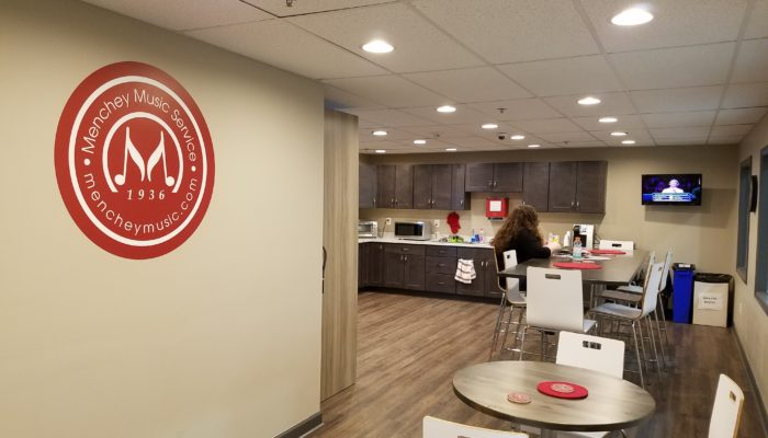 Breakroom featuring Menchey Music logo on wall.