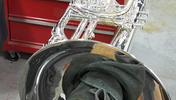 Silver trumpet being polished.