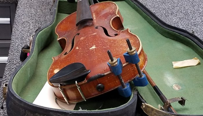Violin without bridge or strings sitting on a green case.