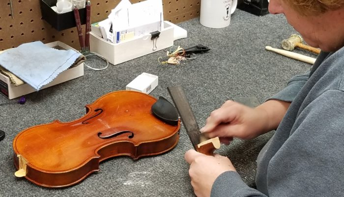 Repair technician working to repair the neck of a violin which has come apart.
