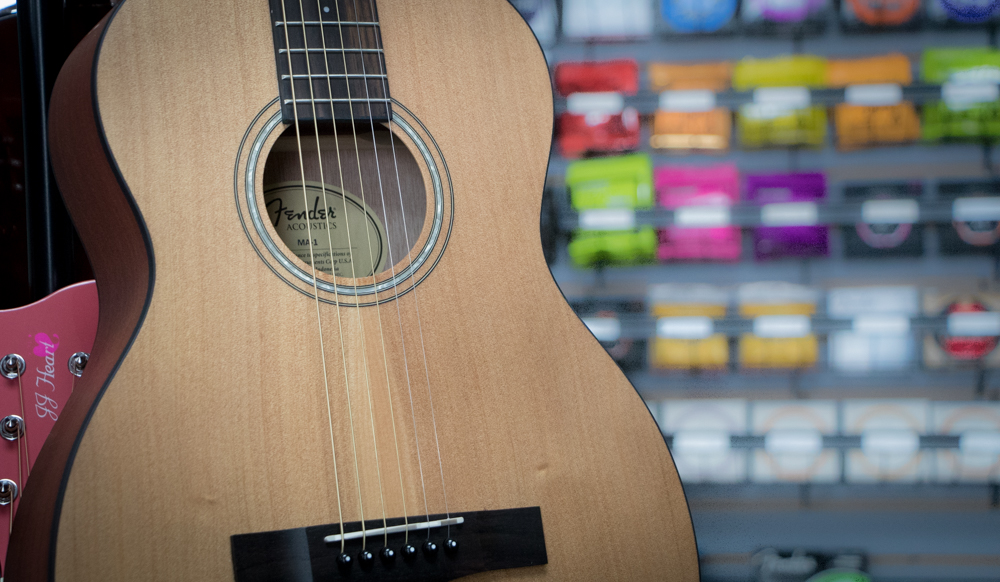 Fender acoustic guitar and music products blurred in background.