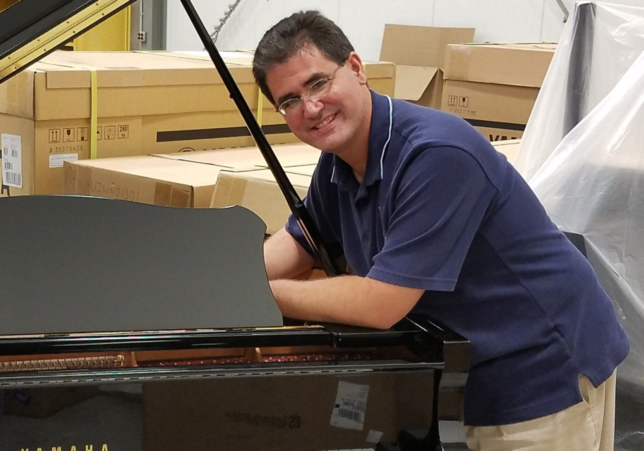 Piano repair technician tuning a grand piano with boxed pianos behind him.
