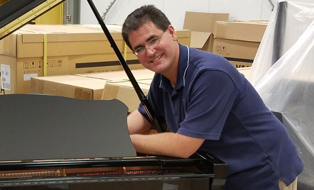 Piano technician tuning a Yamaha grand piano.