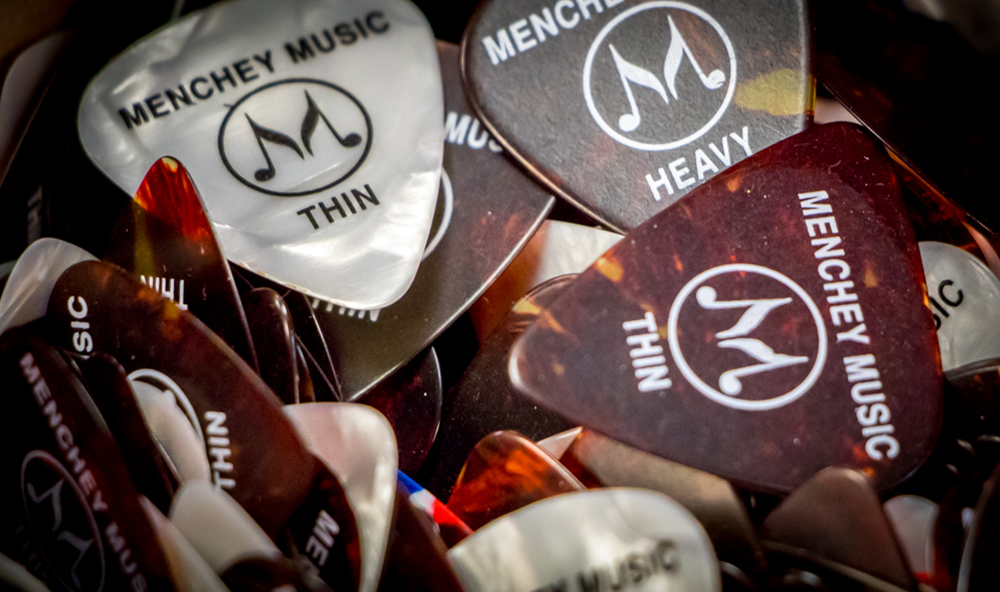 Menchey Music picks in varying colors and thicknesses.