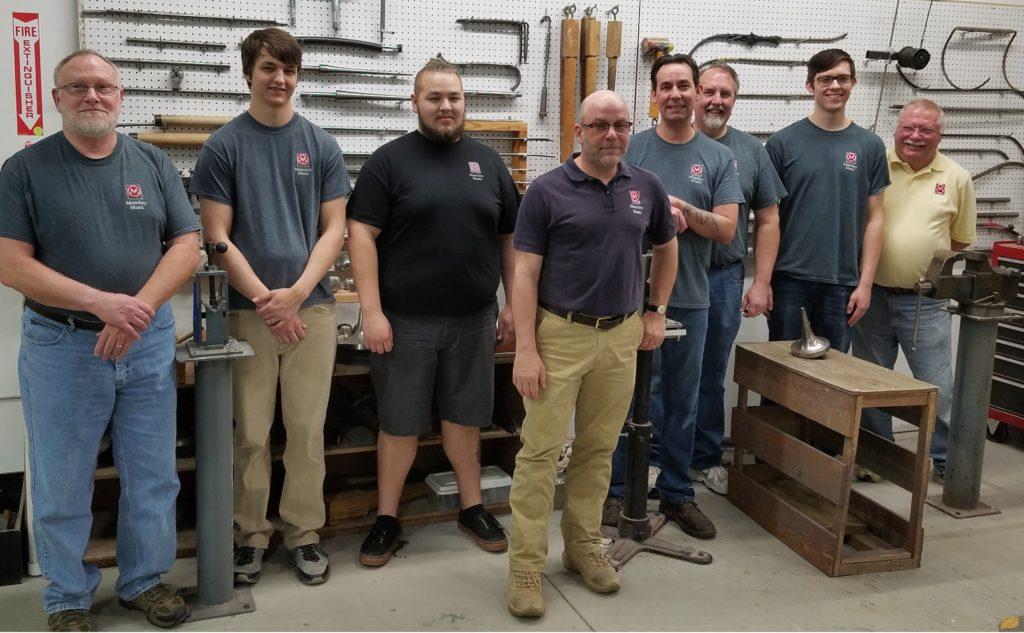 8 instrument repair technicians with repair tools hanging behind them.