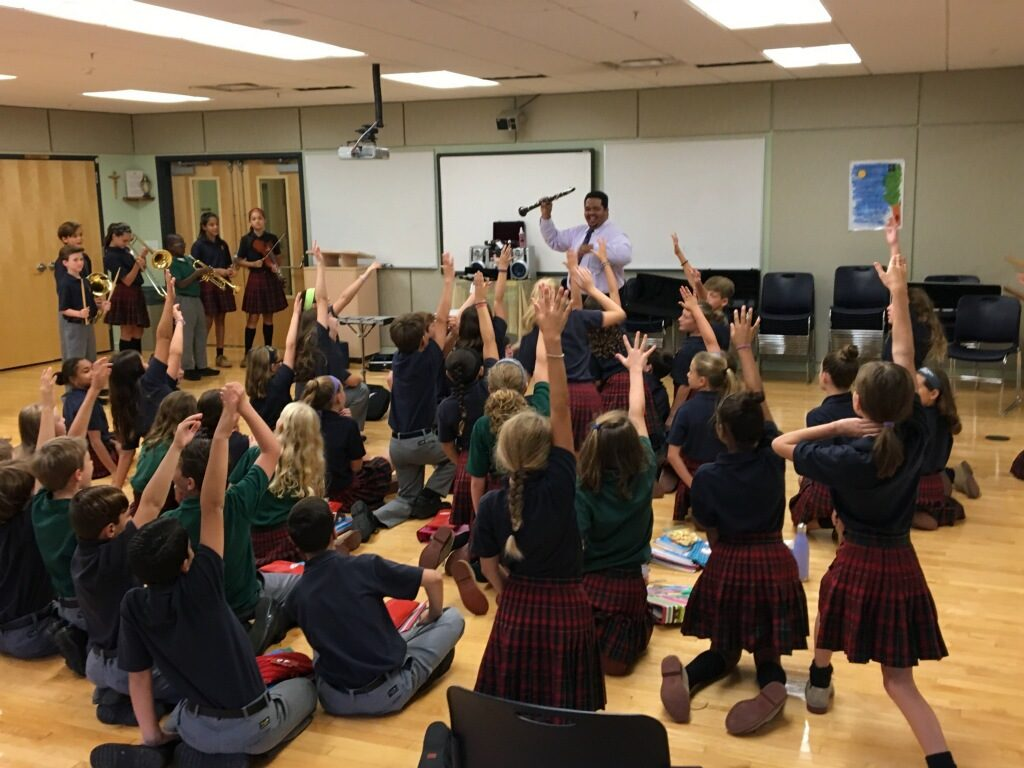 Teacher holding a clarinet in front of a class of students sitting on the floor.