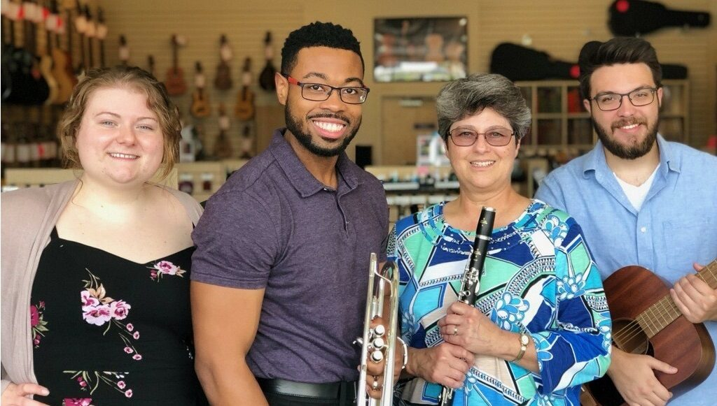 Two women and two men in our store, one holding a clarinet, trumpet and guitar.