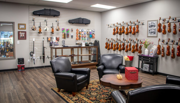 Room with seating area and violins and string accessories  displayed on wall.