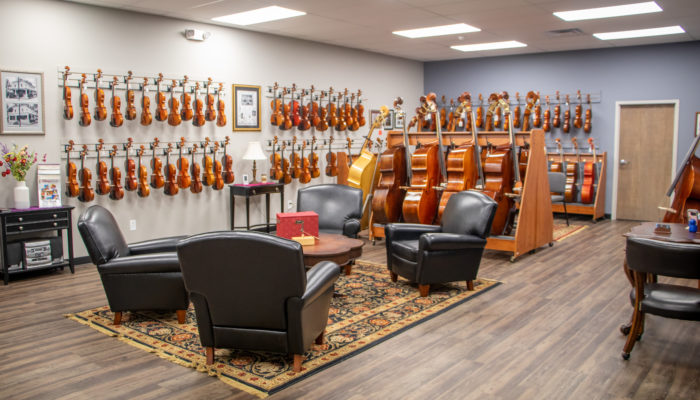 Large room with seating area and numerous cellos, violins and violas.