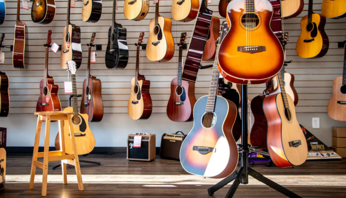 Yamaha, Ibanez and Martin acoustic guitars on floor and wall displays.