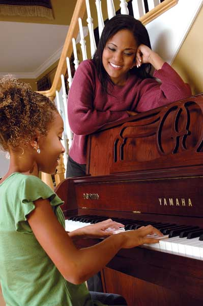 Mother watching daughter practice for piano lessons.