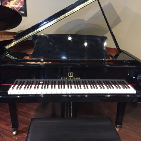 Used polished ebony grand piano with lid fully extended.