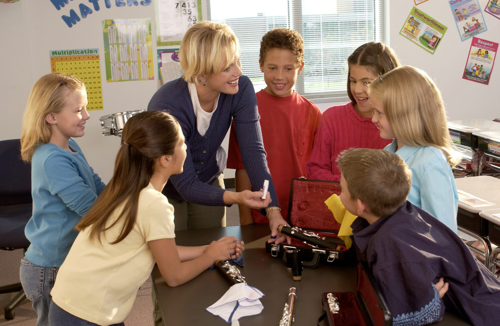 Teacher with her class gathered around a rental instrument at a table showing her class how to put a clarinet together.