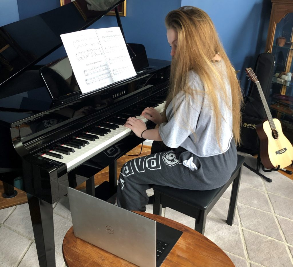 Girl sitting at piano taking online music lesson