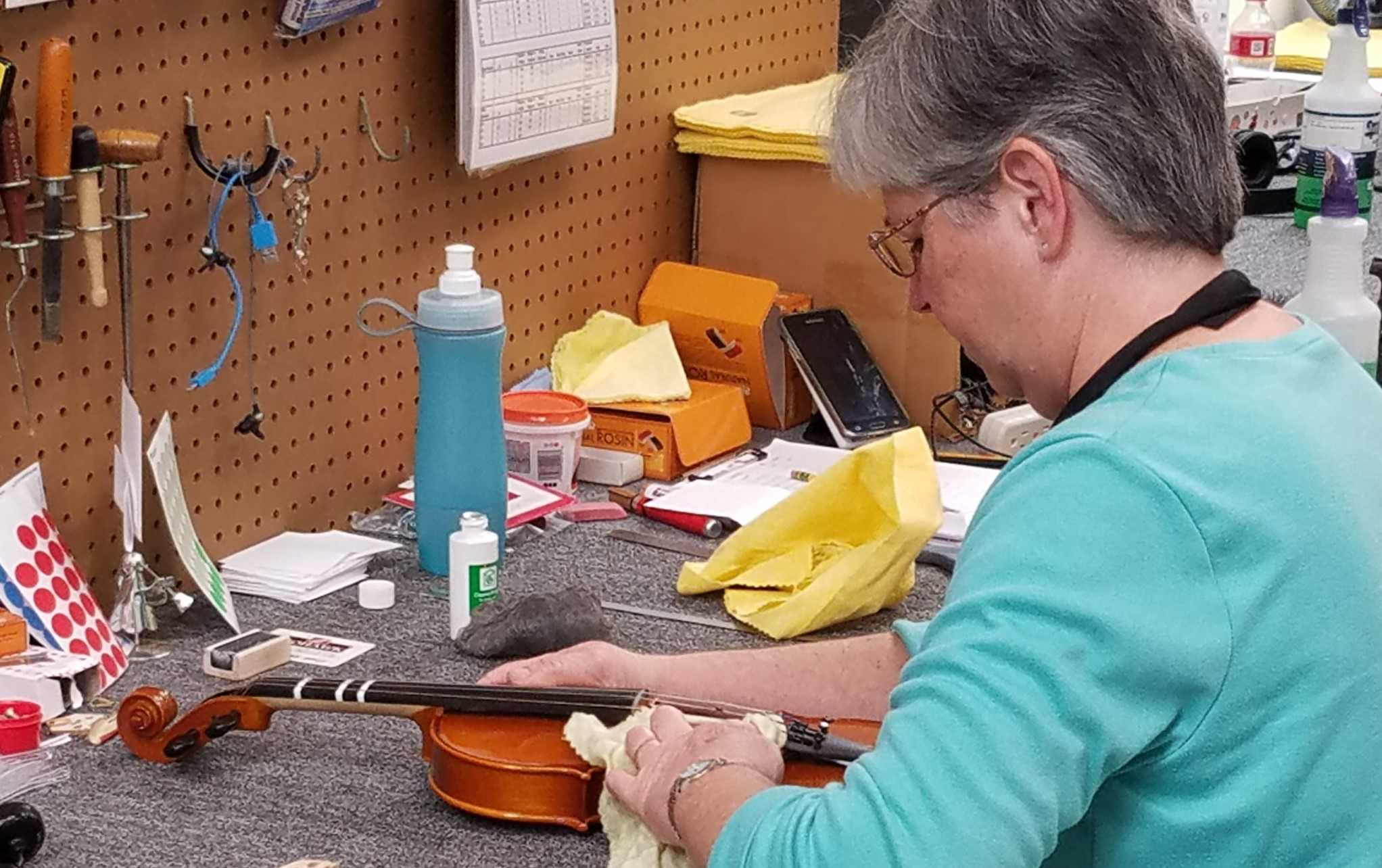 Woman cleaning violin and removing rosin after playing her instrument