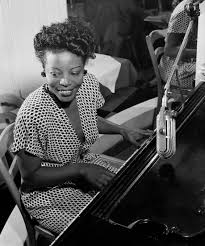 Mary Lou Williams smiles while playing the piano.