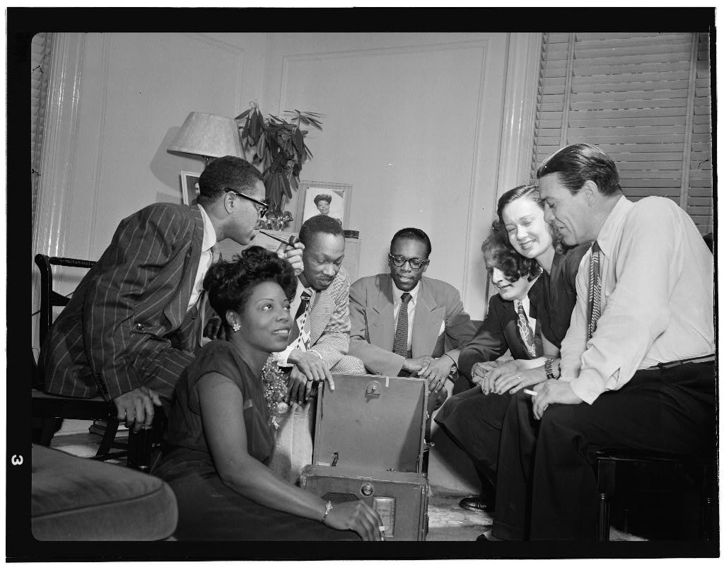 Mary Lou Williams with a group of colleagues around a record player.