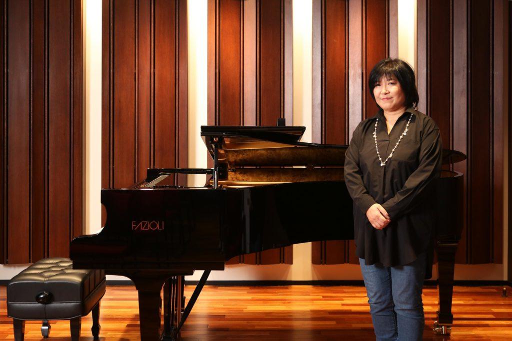 Yoko Shimomura poses in front of piano for portrait.